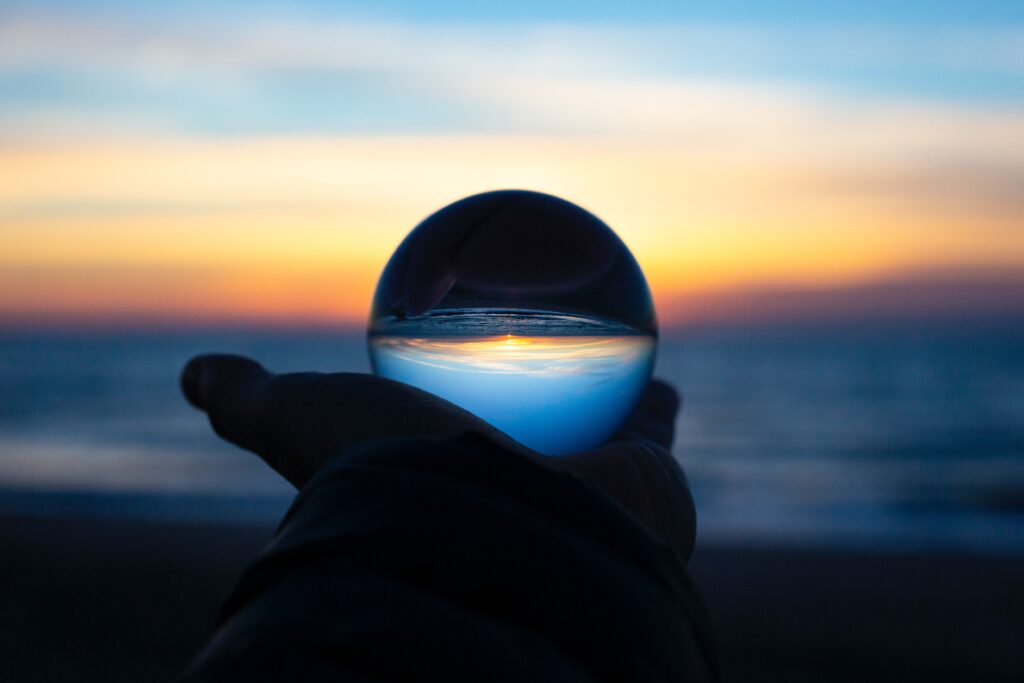 Crystal ball being held in front of an ocean view