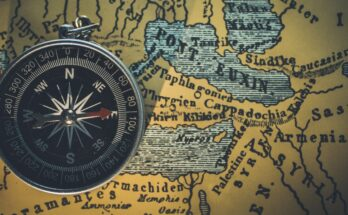 Photo of a compass sitting on top of a map